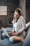 Woman having conversation on smartphone and typing on laptop at home. Woman during work at home office Stock Photo