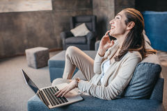Woman having conversation on smartphone during work on laptop at home, home business concept. Portrait of woman having conversation on smartphone during work on stock photography
