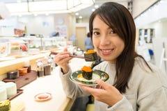 Woman having Conveyor belt sushi Royalty Free Stock Images