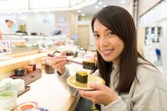 Woman having Conveyor belt sushi Royalty Free Stock Image