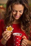 Woman having cup of chocolate and cookie in Christmas kitchen Stock Images