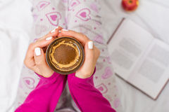 Woman having a cup of coffee in bed Stock Images