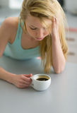 Woman having cup of coffee in kitchen after sleep Stock Image