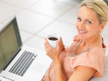 Woman having a cup of coffee and using a laptop Royalty Free Stock Image