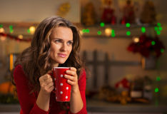 Woman having cup of hot chocolate in Christmas decorated kitchen Royalty Free Stock Photos