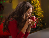 Woman having cup of hot chocolate and cookie near Christmas tree Royalty Free Stock Photo