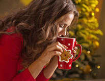 Woman having cup of hot chocolate and cookie near Christmas tree Stock Photo