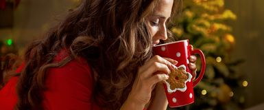 Woman having cup of hot chocolate and cookie near Christmas tree Stock Photography