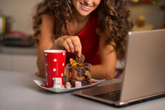 Woman having cup of hot chocolate with cookies and using laptop Stock Photography
