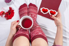 Woman having a cup of tea in bed Royalty Free Stock Images