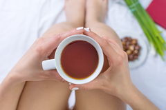 Woman having a cup of tea in bed Royalty Free Stock Photo