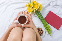 Woman having a cup of tea in bed Royalty Free Stock Image