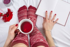 Woman having a cup of tea in bed Stock Image