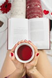 Woman having a cup of tea in bed Stock Photography