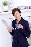 Woman having a cup of tea and reading the newspaper Royalty Free Stock Image