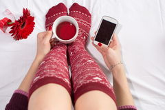 Woman having a cup of tea and texting Stock Images