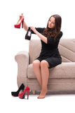 The woman having difficult choice between shoes Royalty Free Stock Image