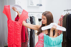 Woman having difficulties choosing dress Royalty Free Stock Images