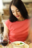 Woman having dinner in restaurant. Portrait of girl in red dress eating and drinking red wine Stock Photos