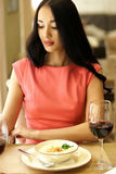 Woman having dinner in restaurant. Portrait of girl in red dress eating and drinking red wine Royalty Free Stock Photo