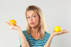 Woman having doubts between lemon and orange for beauty diet. Natural vitamins concept - thinking young blond woman having doubts between lemon and orange held royalty free stock photography