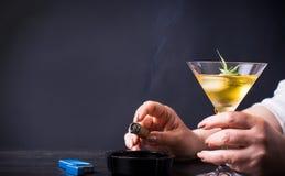 Woman having a drink and smoking. At the bar Royalty Free Stock Photos