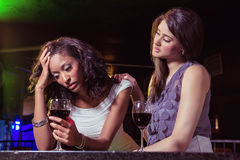 Woman having drinks and comforting her depressed friend Stock Photo