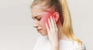 Woman having ear pain, touching her painful head royalty free stock image