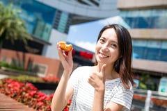 Woman having egg tart in Hong Kong Stock Photography