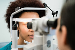 Woman having eyes measured with refractometer. At optician or ophthalmologist Stock Photos