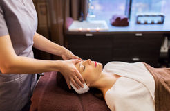 Woman having face and head massage at spa parlor. People, beauty, lifestyle and relaxation concept - beautiful young woman lying with closed eyes and having face stock images