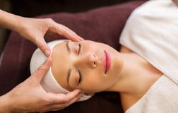 Woman having face and head massage at spa Stock Images