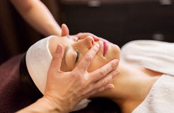 Woman having face and head massage at spa. People, beauty, lifestyle and relaxation concept - beautiful young woman lying with closed eyes and having face and stock photos