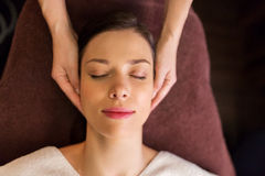 Woman having face and head massage at spa. People, beauty, lifestyle and relaxation concept - beautiful young woman lying with closed eyes and having face and stock images