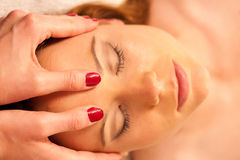 Woman having face massage treatment in wellness stock photo