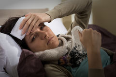 Woman having fever holding her forehead Royalty Free Stock Images