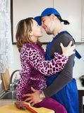 Woman having flirt with plumber. At kitchen royalty free stock photo