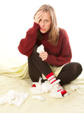 Woman having flu. Young girl suffering from influenza,  holding a handkerchief because of coughing Royalty Free Stock Images
