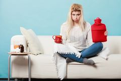 Woman holding hot water bottle and tea in cup Royalty Free Stock Image