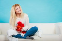 Woman holding hot water bottle and tea in cup Stock Photo