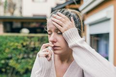 Woman is having flu and she is using nasal spray to help herself. Woman using nasal spray. Nasal spray to help a cold. Sick with a rhinitis woman dripping nose Royalty Free Stock Photography