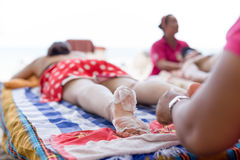 Woman having foot scrub on the beach Royalty Free Stock Photos