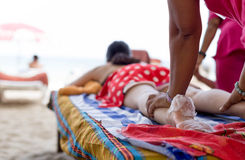 Woman having foot scrub and massage on the beach Royalty Free Stock Photography