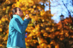 Woman having fun blowing bubbles in autumnal park Stock Photography
