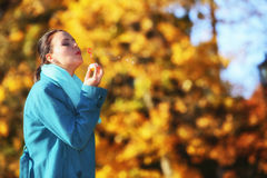 Woman having fun blowing bubbles in autumnal park Stock Photos