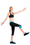 Woman having fun doing zumba fitness. Raising leg and arms Stock Photography
