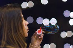 Woman having fun making soap bubbles at night party or new year eve celebration. Woman having fun making soap bubbles at night party royalty free stock photos