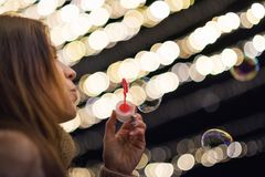 Woman having fun making soap bubbles at night party or new year eve celebration. Woman having fun making soap bubbles at night party stock photography