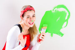 Woman having fun painting wall Royalty Free Stock Image