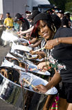 A woman having fun and playing steel drums. A woman from CIS Band Trust enjoying herself and playing steel drums at the Notting Hill Panorama Championships in stock images